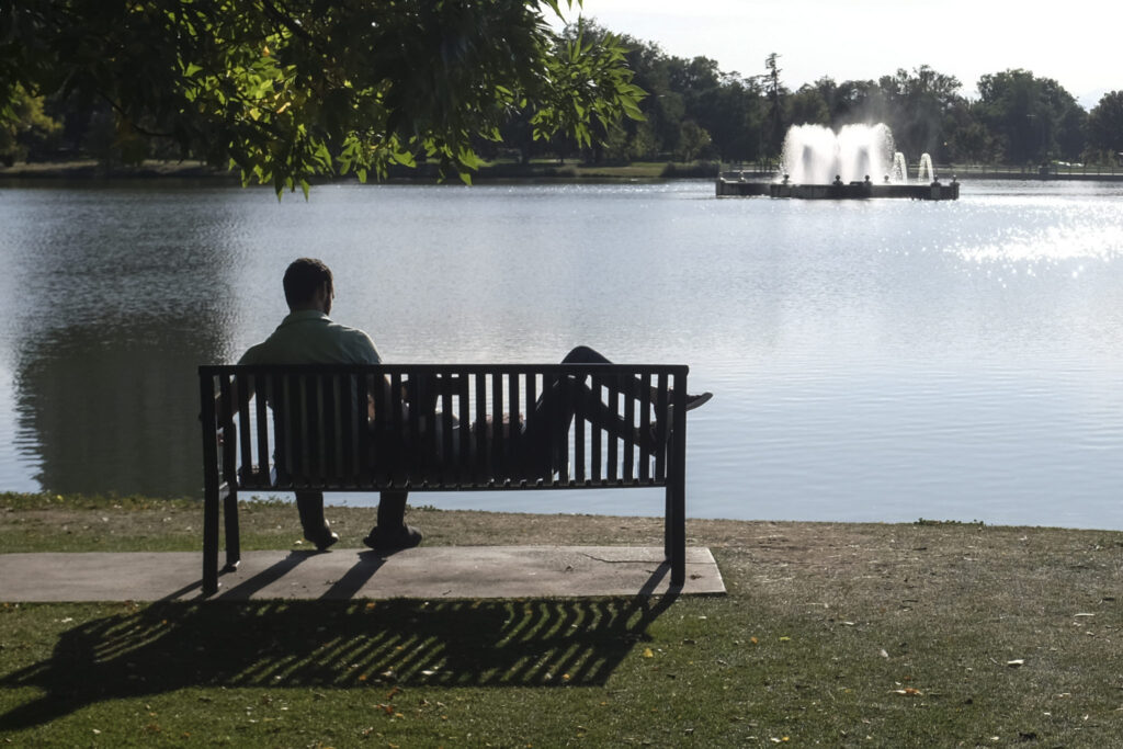 A couple sits at the edge of the lake at City Park in central Denver on Sept. 28 2020. In a typical year, about 48 percent of Denver's water comes from the Western Slope.