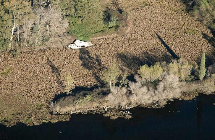 Invasive aquatic vegetation surrounds an abandoned boat in the Delta. (Source: California Department of Water Resources)